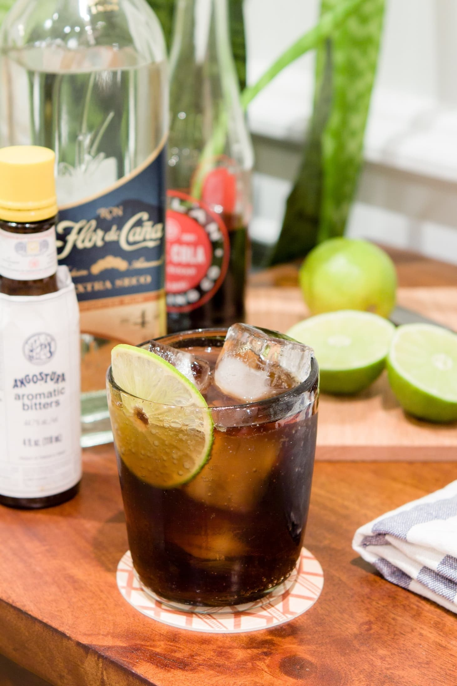 A Cuba libre cocktail garnished with lime.