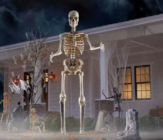 A twelve foot tall skeleton with light up eyes looms in front of a house