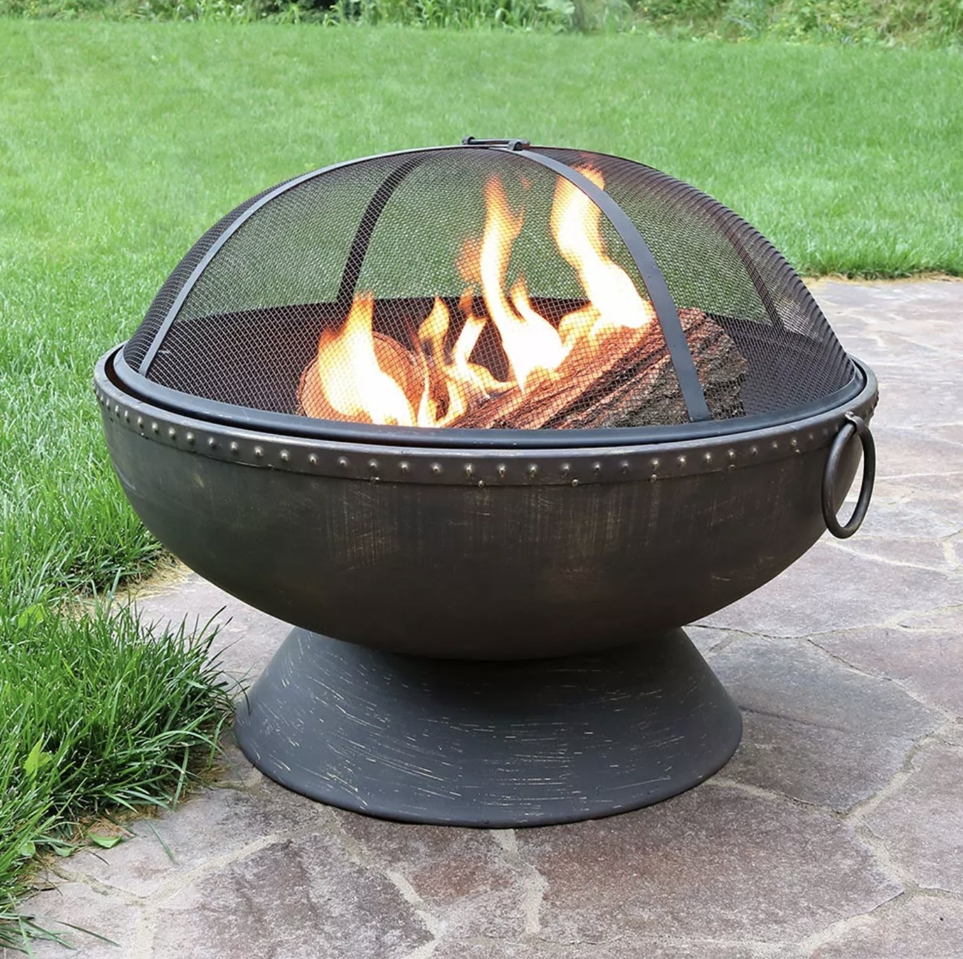 A firepit with fire inside in a backyard