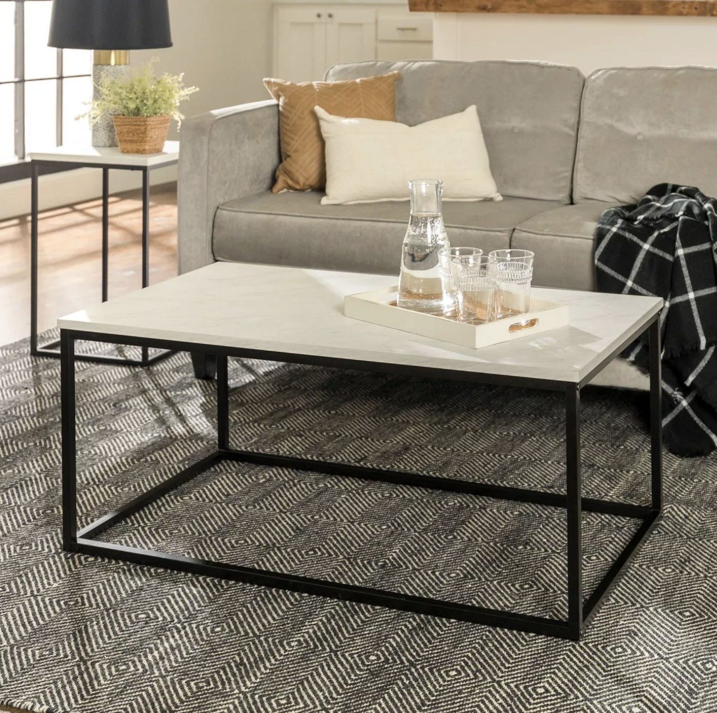 A black box frame coffee table with a faux marble tabletop