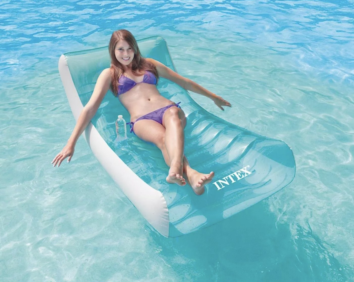 Model is lounging in a pool floating raft chair in a pool