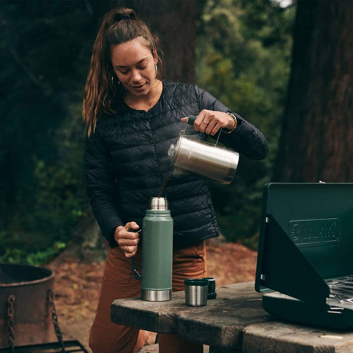 a person pouring a hot beverage into the wide-mouth thermos