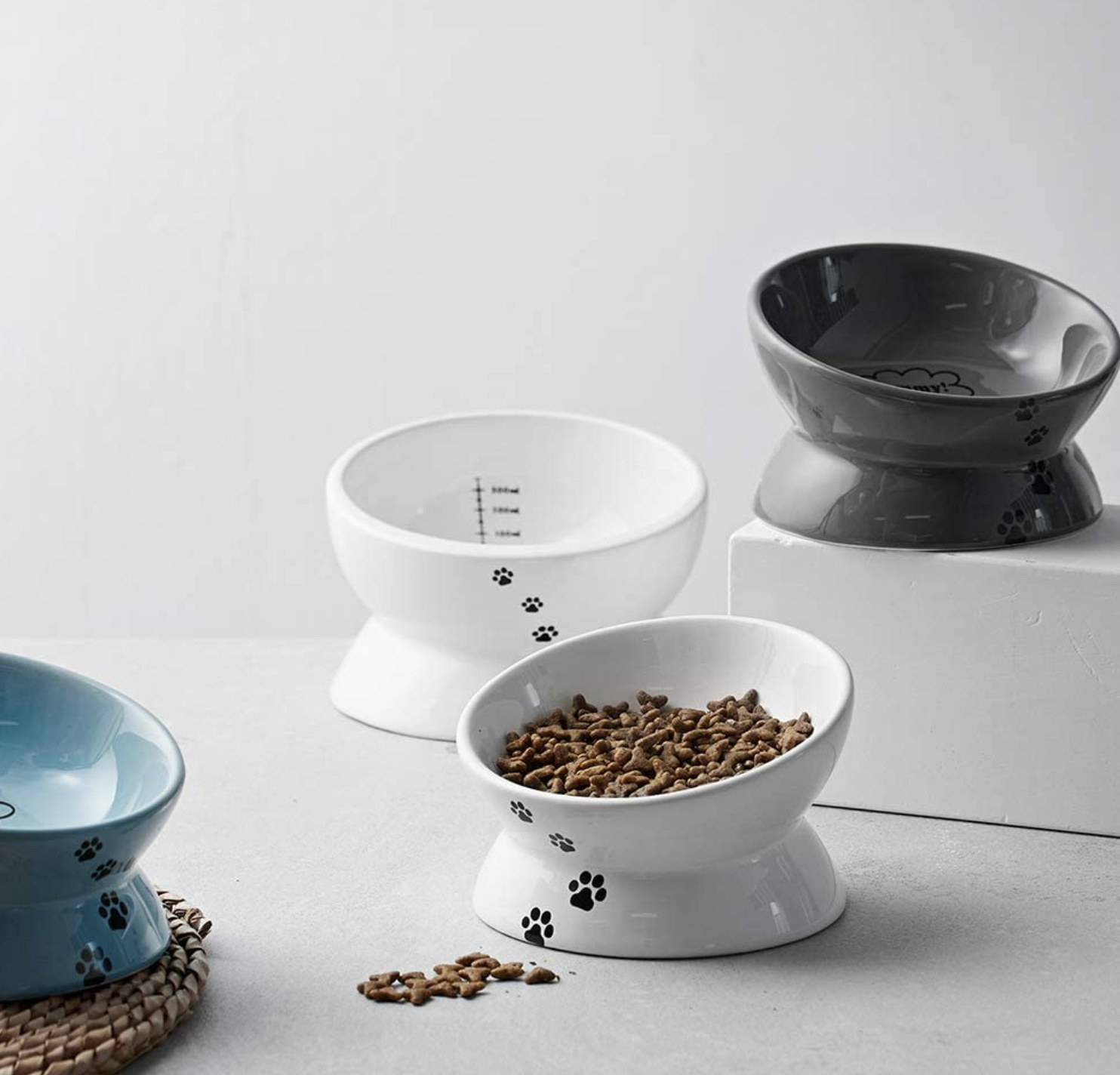 titled cat food bowls with paw prints on the outside of them and measurements on the inside of them. There are two white bowls, one blue bowl, and one grey bowl. One of the white bowls contains dry food