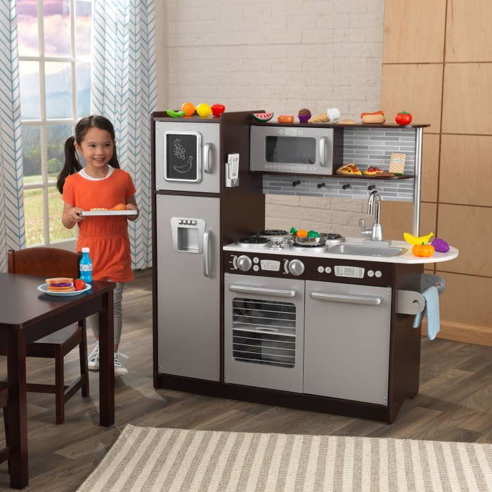 kid smiling while standing next to a play kitchen set