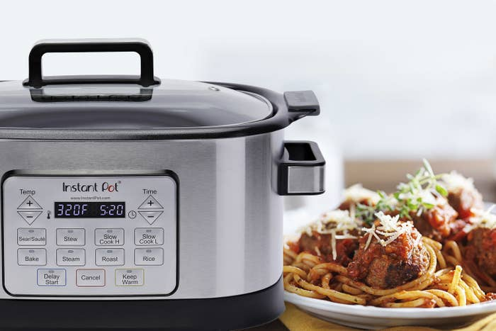 Gray instant pot next to a plate of spaghetti and meatballs