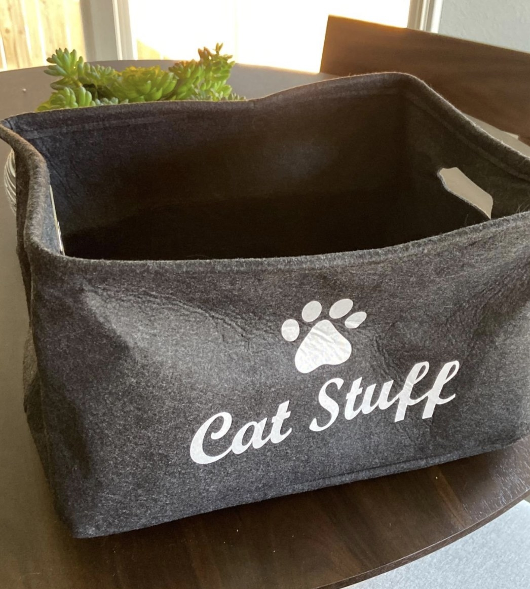 """a storage bin with the words """"cat stuff"""" written on the outside of a bin under a paw print design"""