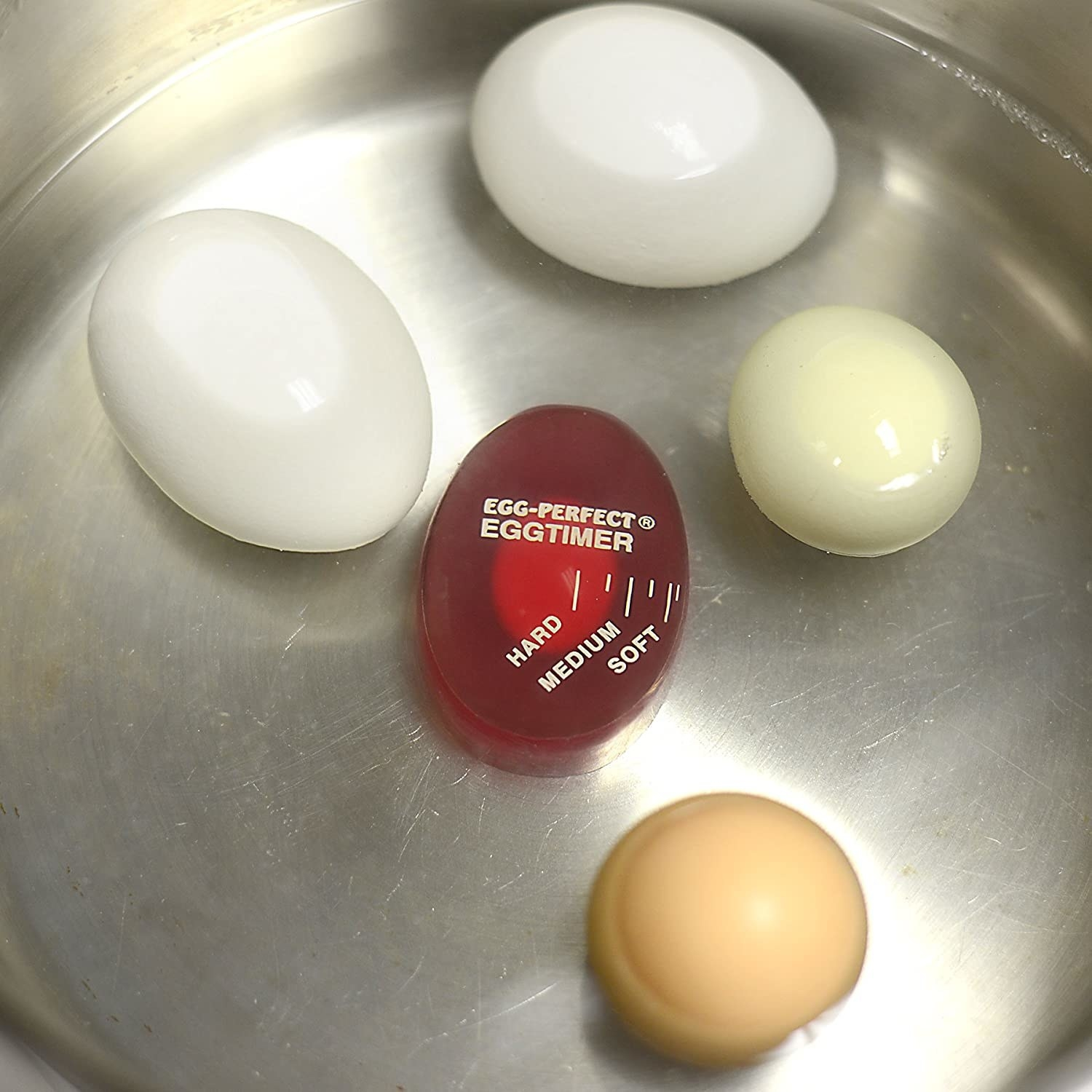 An egg timer in a pot with four eggs.