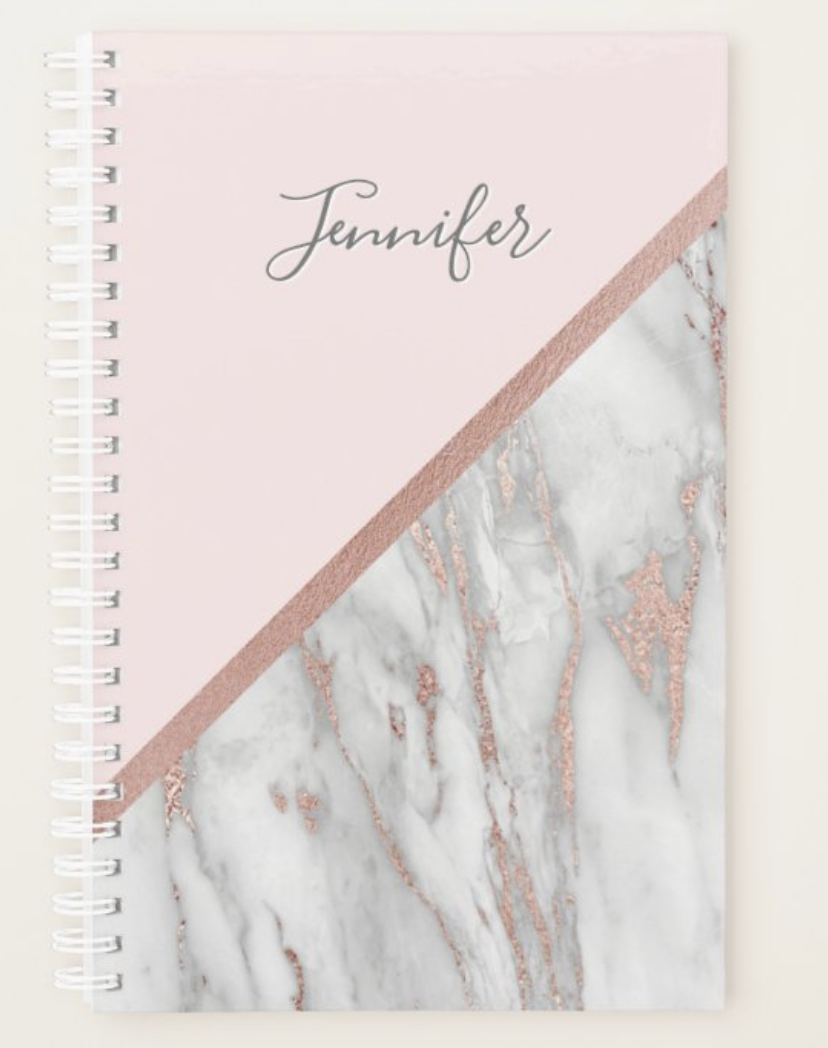 A pale pink and marble patterned planner with a first name at the top