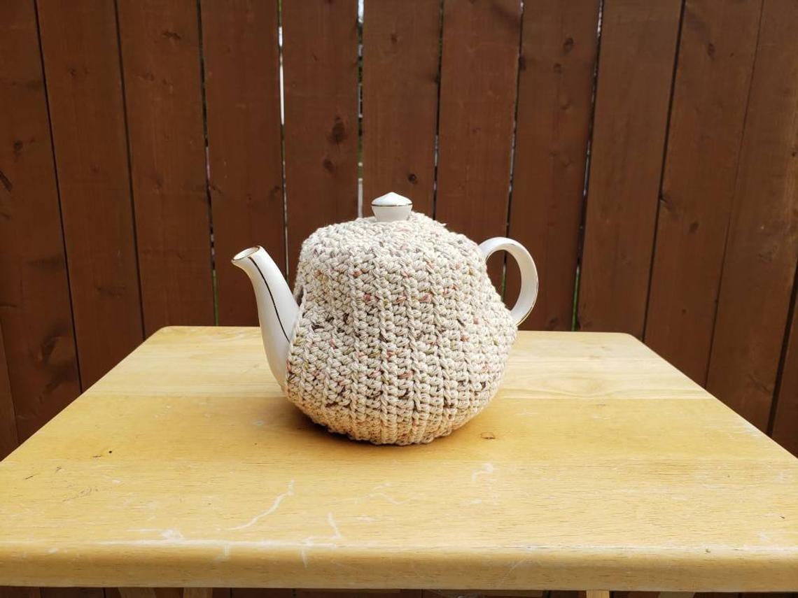 A tea pot with a cozy