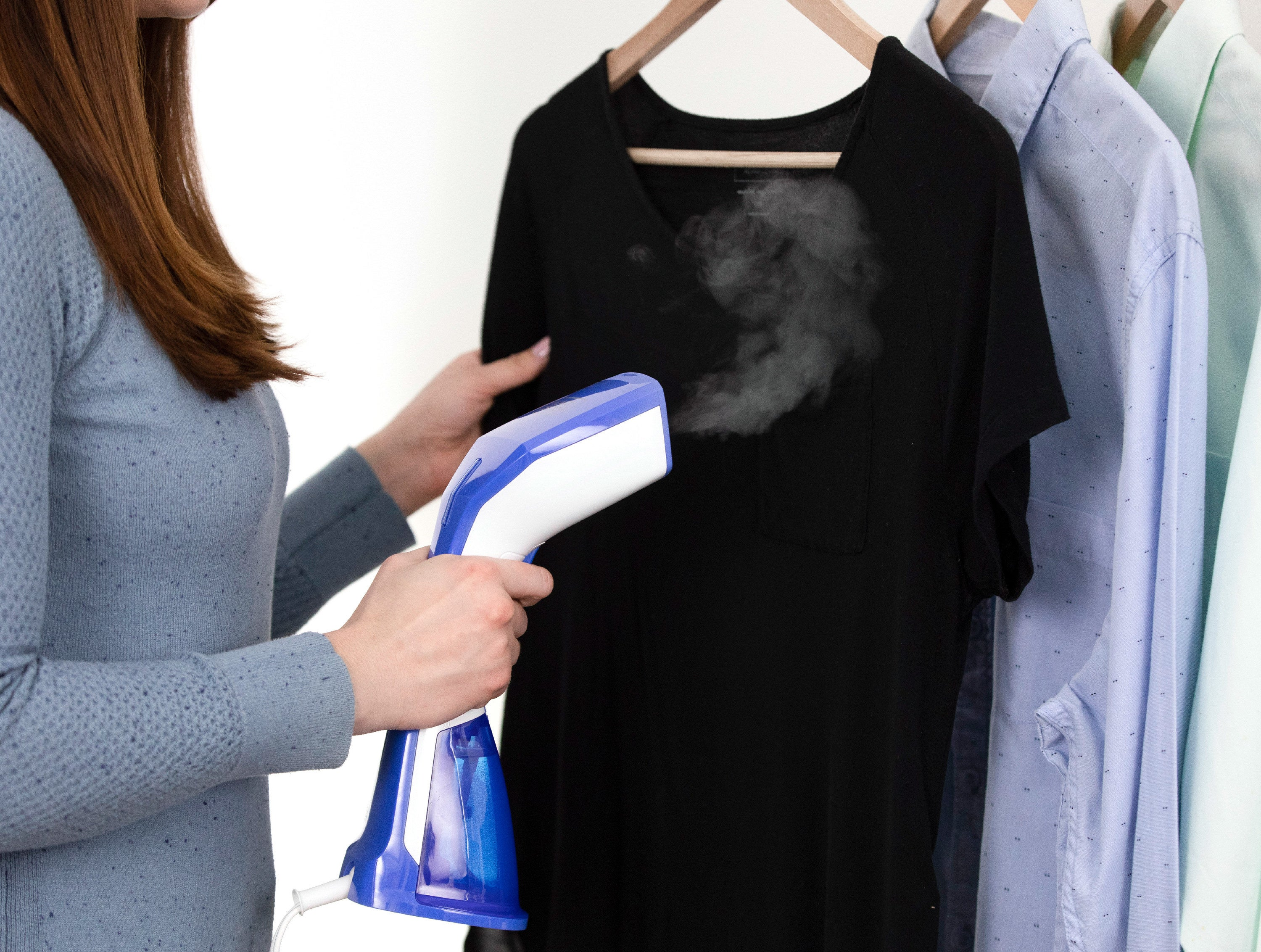 person using a blue and white garment steamer on a black shirt
