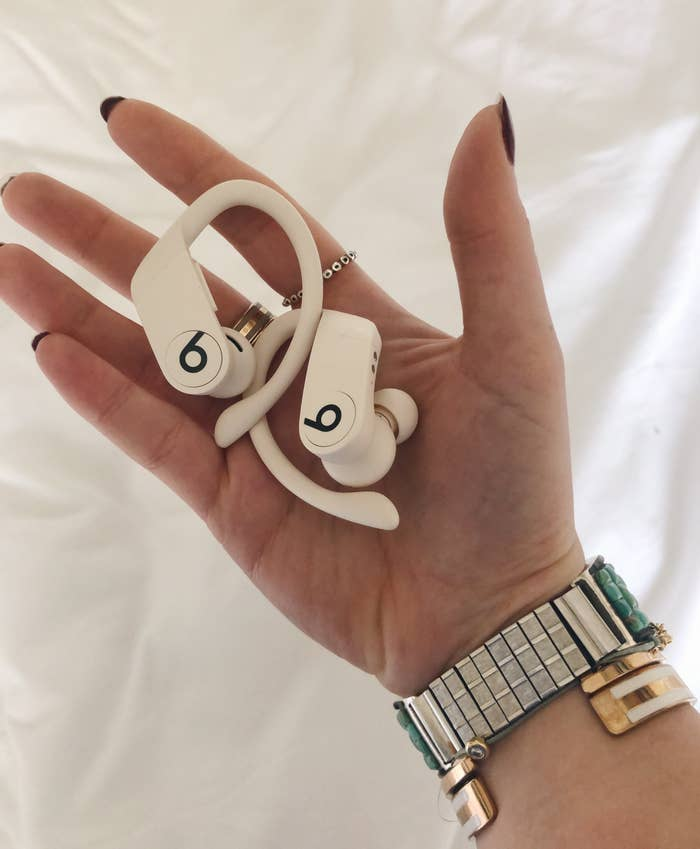 BuzzFeed Shopping reviewer holding their headphones in white