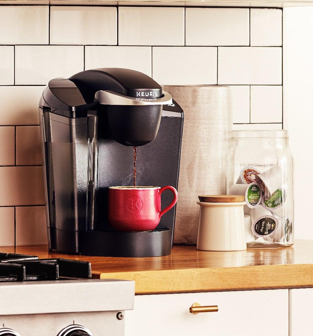 black keurig coffee maker with a red coffee mug underneath