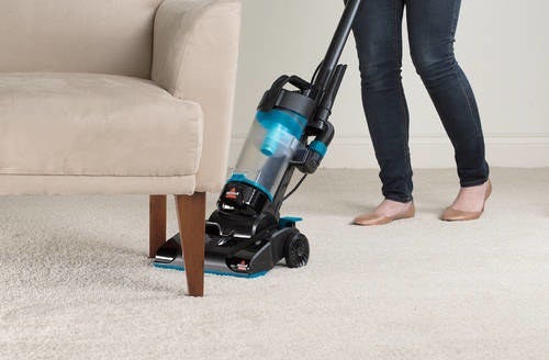 person using bissell vacuum to clean underneath the armchair