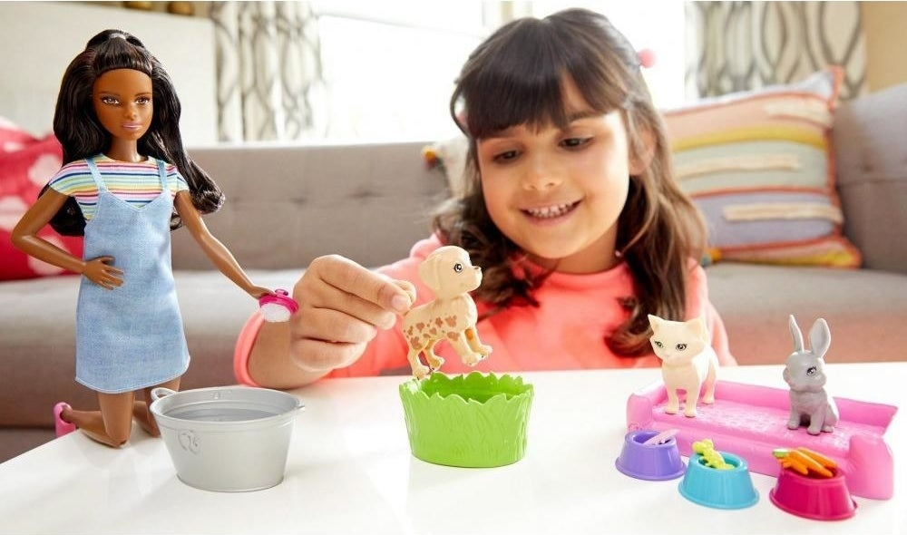 kid playing with a barbie play and wash pets playset