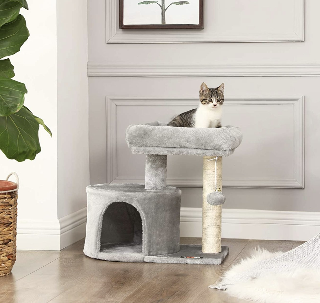 a can with stripes sitting on top of a cat tree that is grey with an ivory scratch post