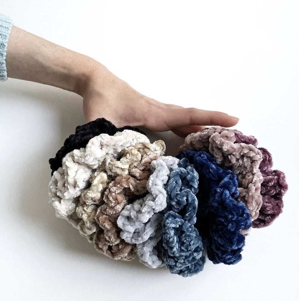 A person holding several velour crocheted scrunchies