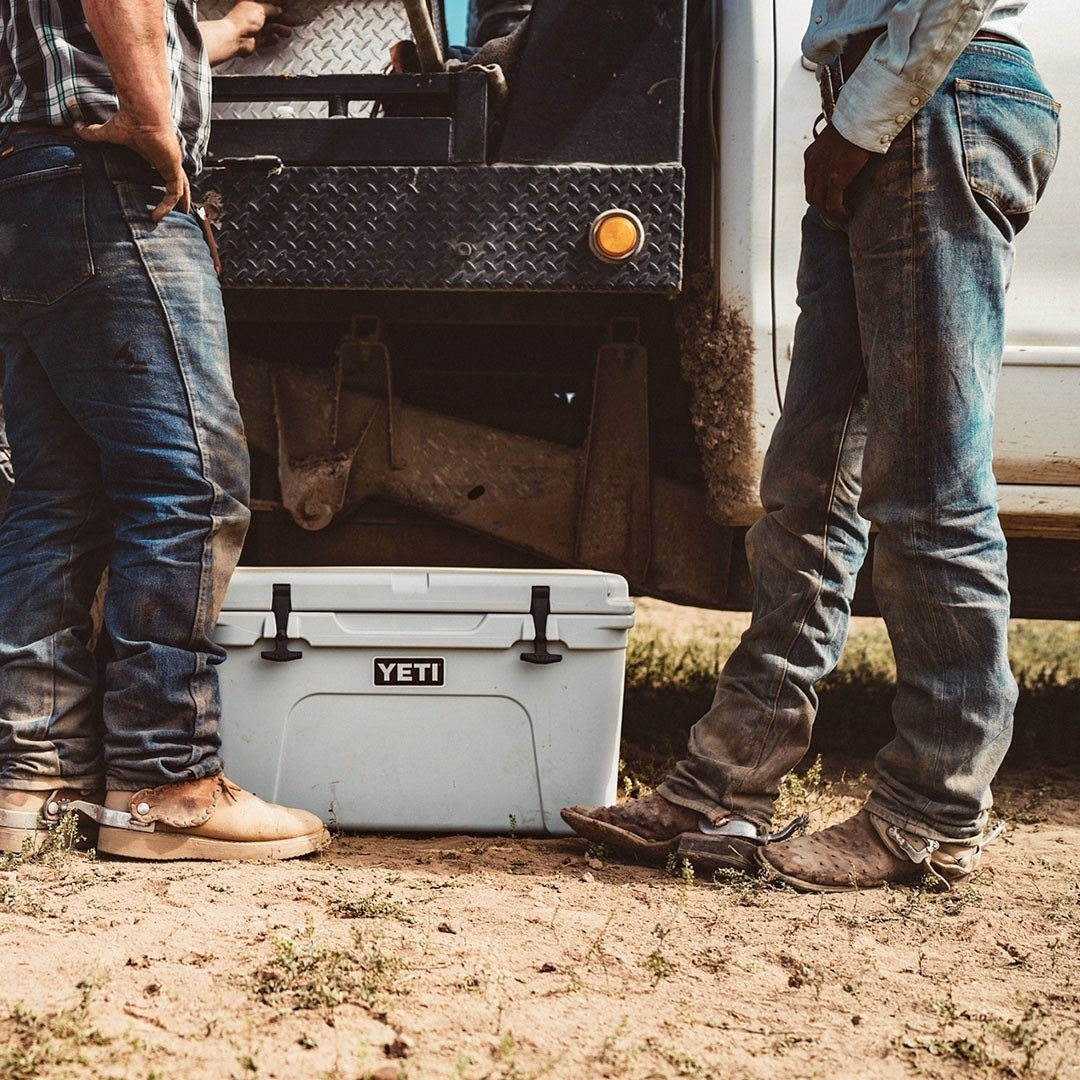the big cooler in a sage green on the ground next to two rugged men's legs