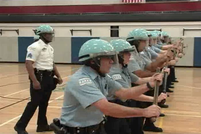 Cops wearing protective gear and holding batons stand in a line in a gymnasium