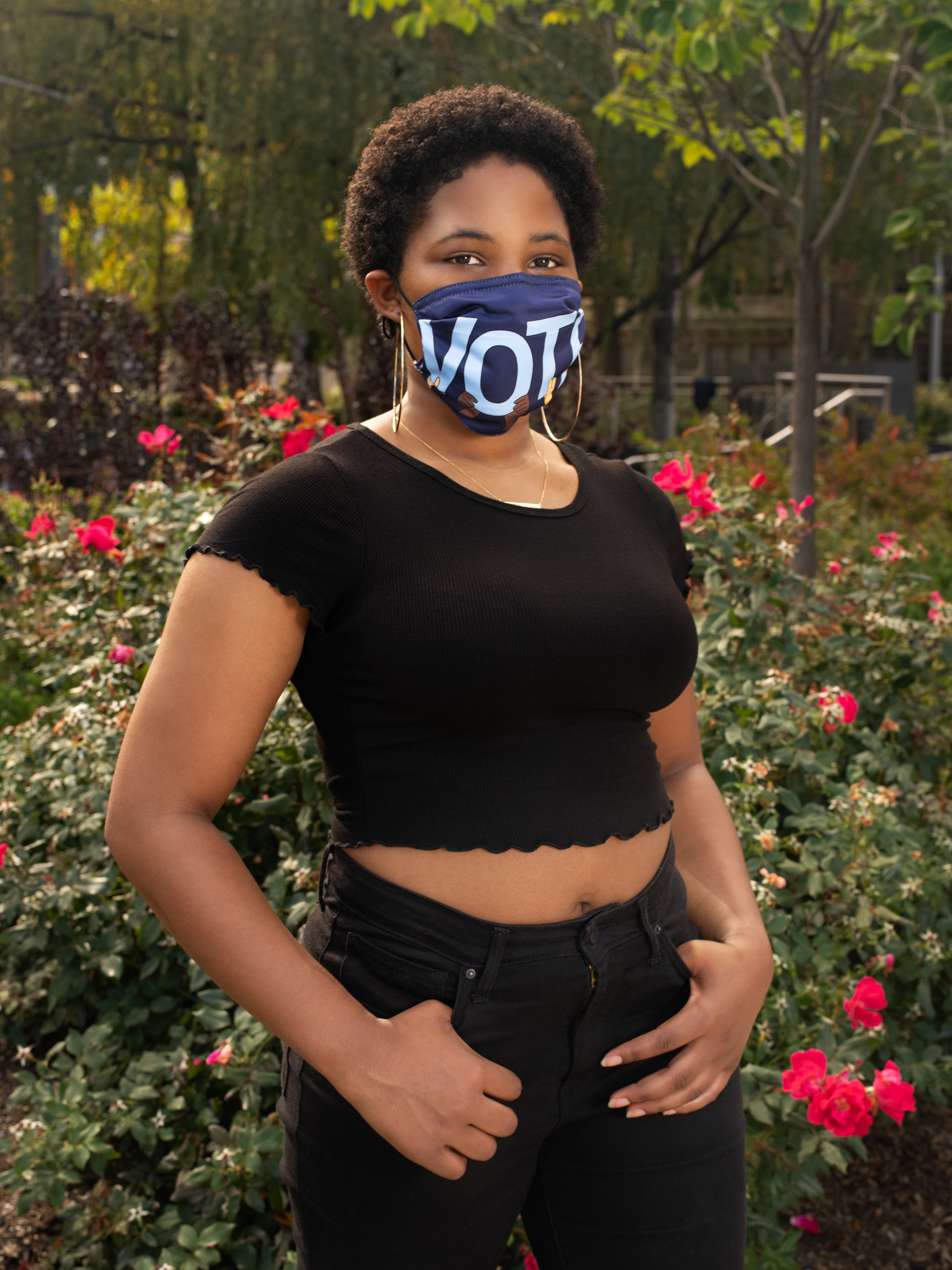 "A female poll worker with a ""Vote"" mask in front of flowers"