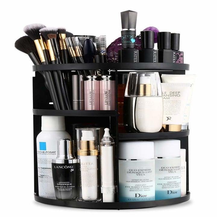 The round multi-shelf organizer holding makeup and brushes