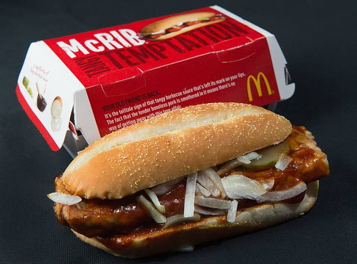 The McRib in front of its container which says 'McRIB Tasty Temptation'