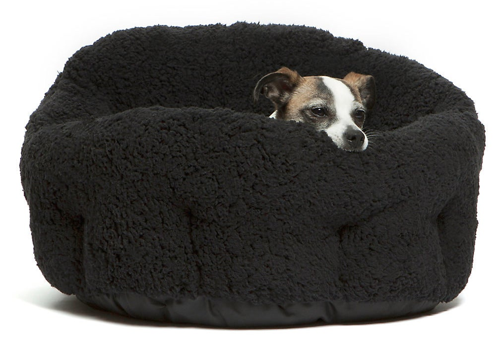 a dog curled up in a black fluffy poof bed