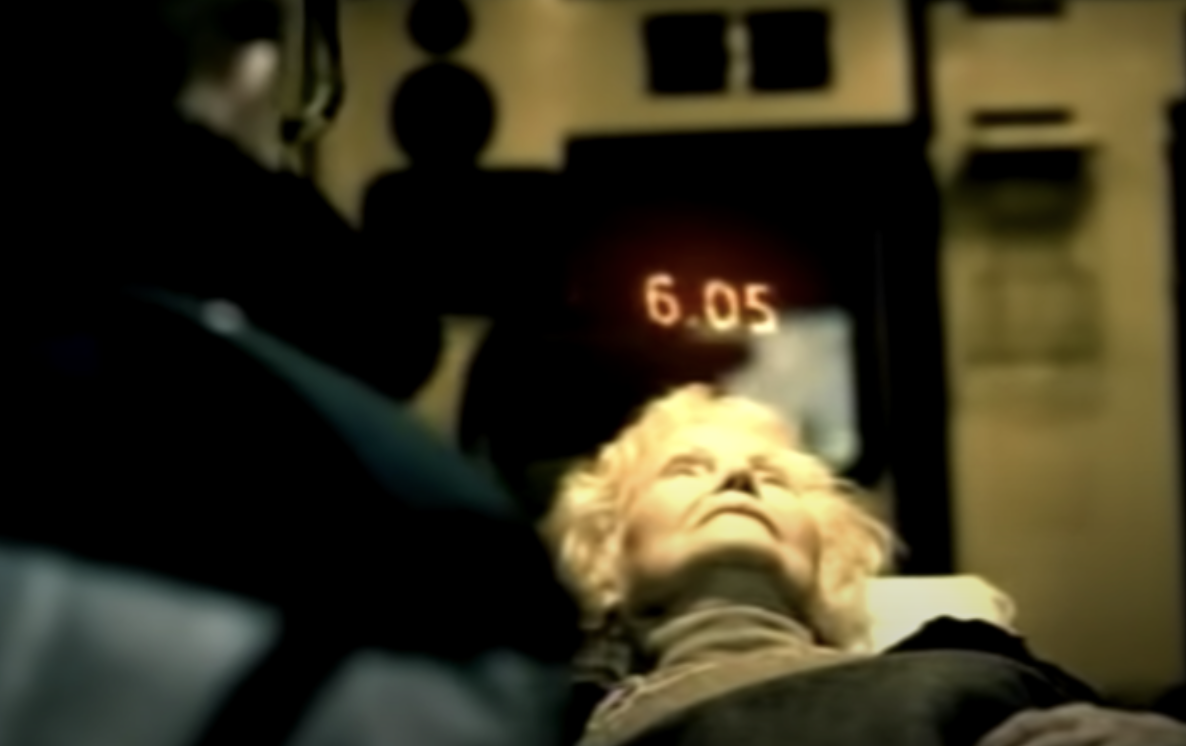 An old women being put on an ambulance with a counter of 6 seconds above her head