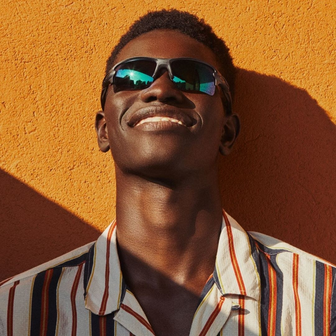 a model wearing black oakley sunglasses with a matte black rip and rimless lenses at the bottom