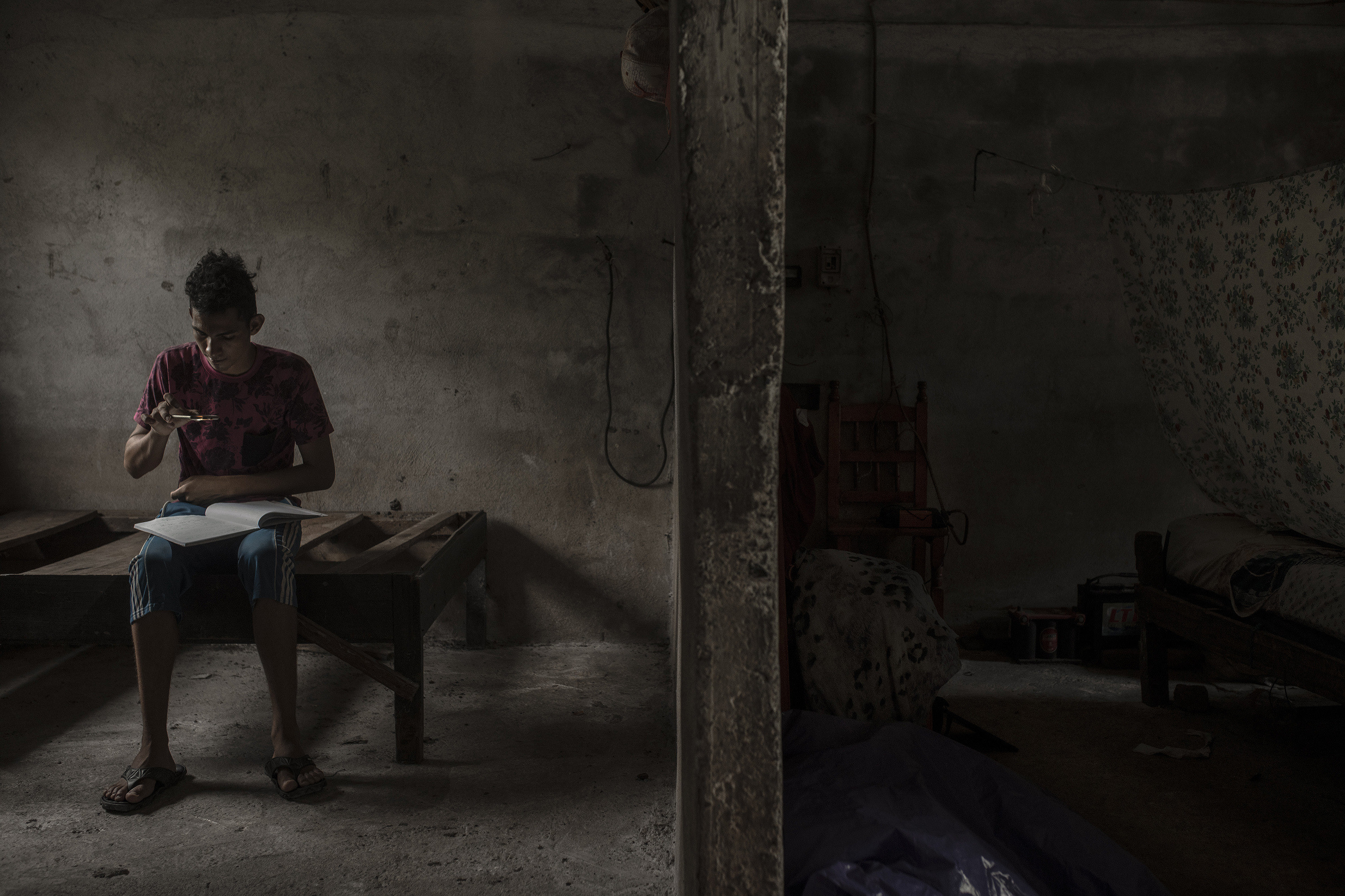 A boy photographs a notebook with his phone at his home in Mexico