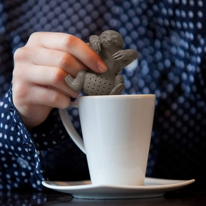 Hand placing sloth-shaped infuser in white coffee mug
