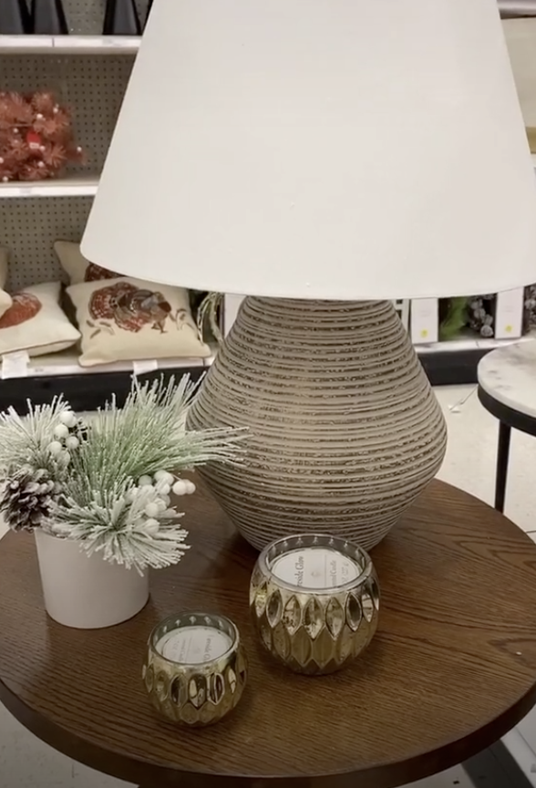 Side circle table with a large lamp, pine cones, and candles