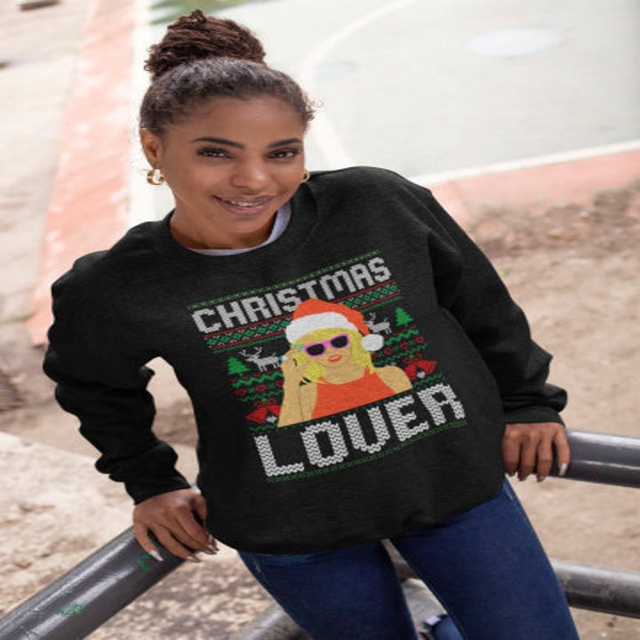 """a model wearing a black sweatshirt with an illustration of taylor swift wearing a santa hat and sunglasses and the words """"christmas lover"""""""