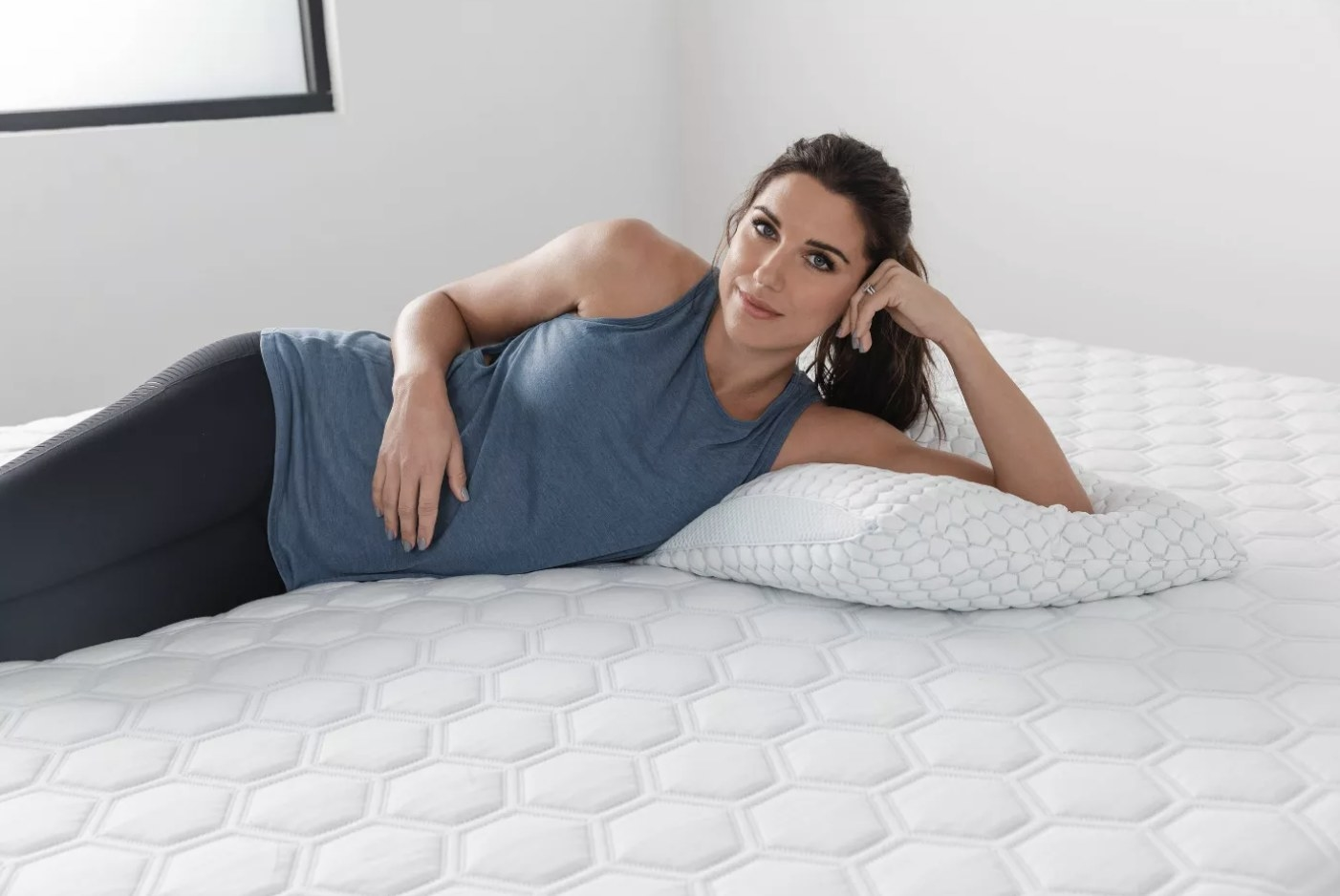 Model is lounging on a foam plllow on a bed