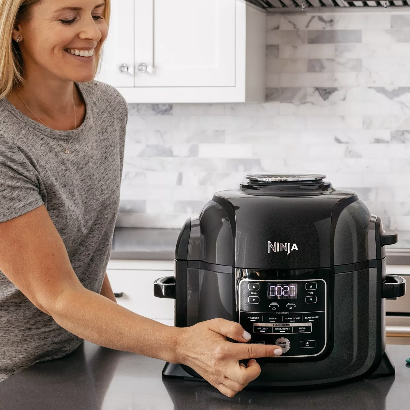 Model is pressing a button on a Ninja pressure cooker and air fryer