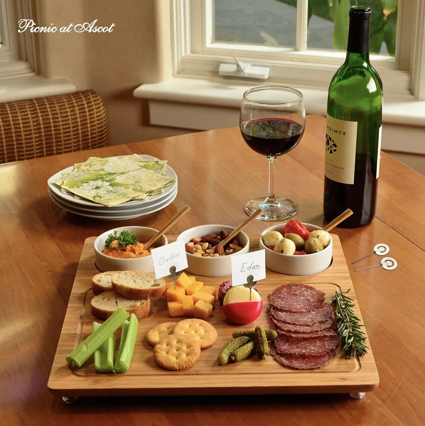 A bamboo cheese board with an assortment of appetizers on top