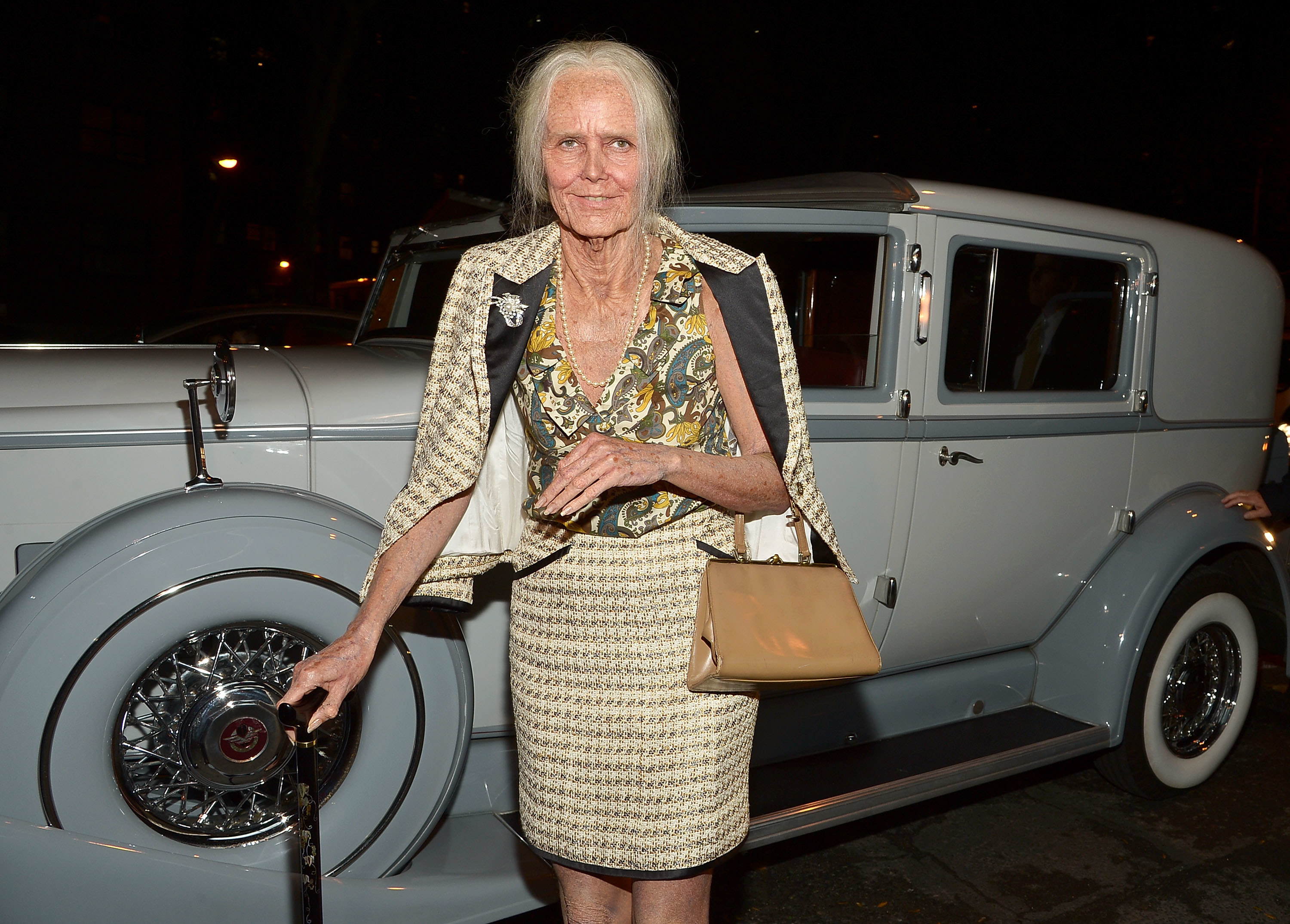 Heidi Klum dressed as an old woman in front of a fancy blue car.