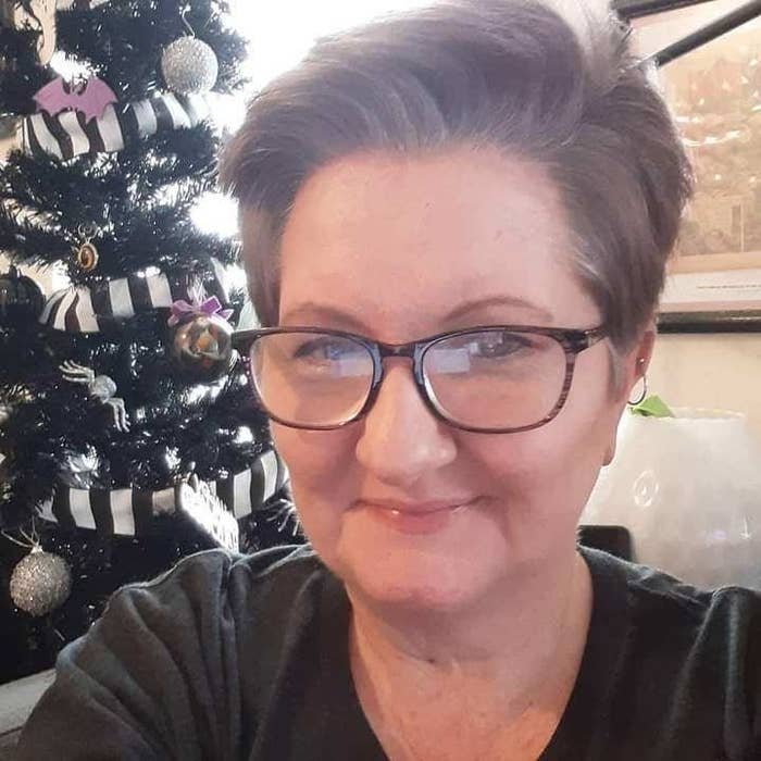 Image of Vicki Landers wearing black rimmed glasses and a small hoop earring on her right ear. She has short dark gray hair that sweeps over the top. Behind her is a decorated Christmas tree and a framed picture on the wall.