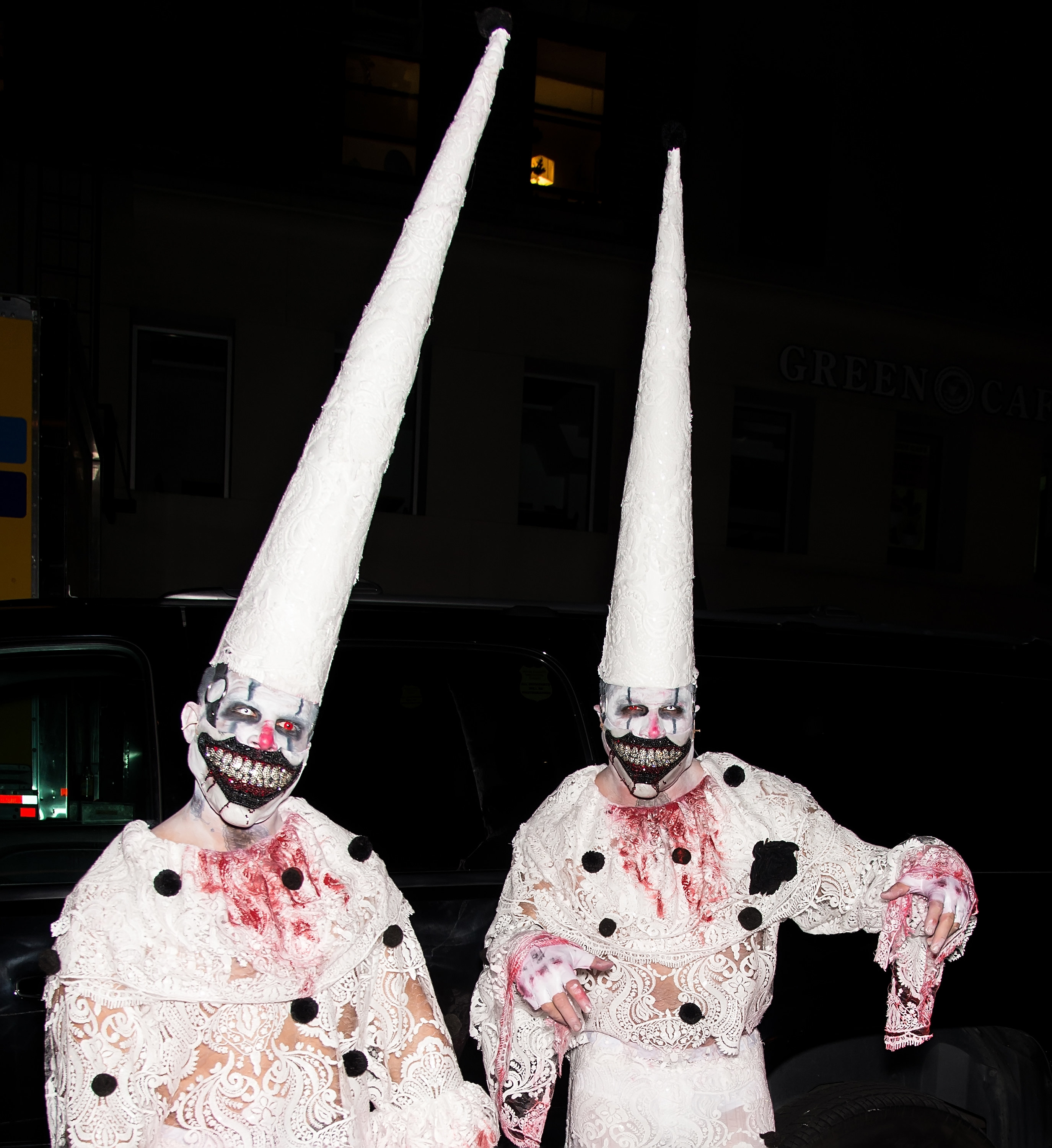 Two men dressed as very creepy clowns with lace suits and pointy hats.