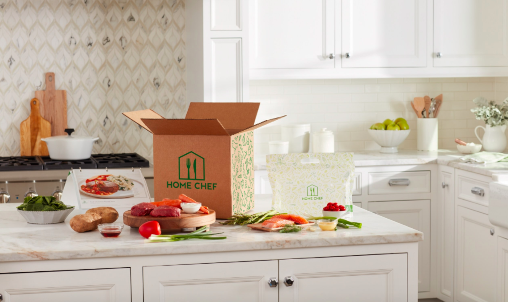 HomeChef Box with recipe ingredients, including veggies, meat, and fish, on a kitchen counter next to a booklet of recipe cards