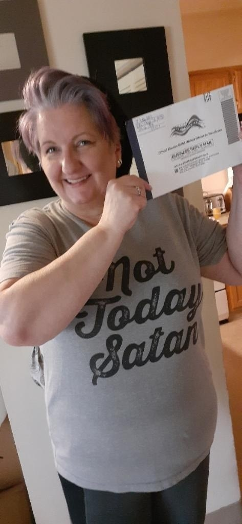 "Image of Vicki Landers wearing a ""Not Today Satan"" t-shirt. She has grey purple hair and is holding her ballot next to her face"