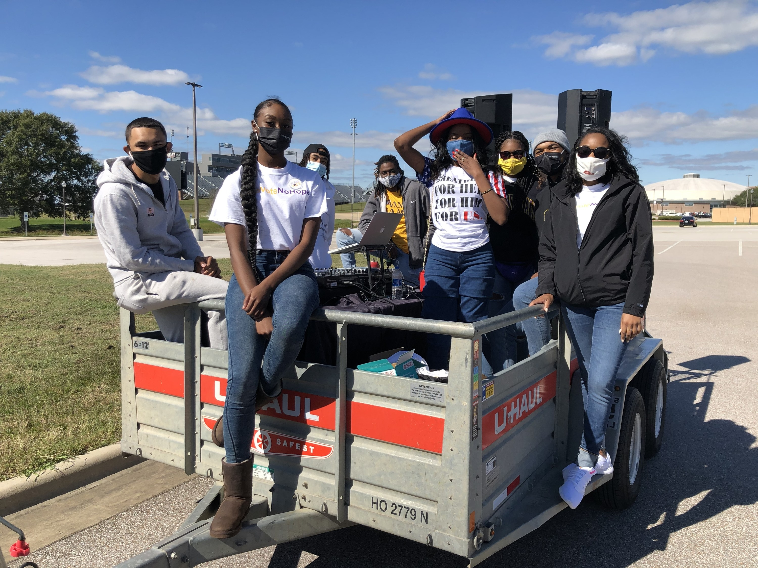 Students wearing masks stand in a U-Haul trailer