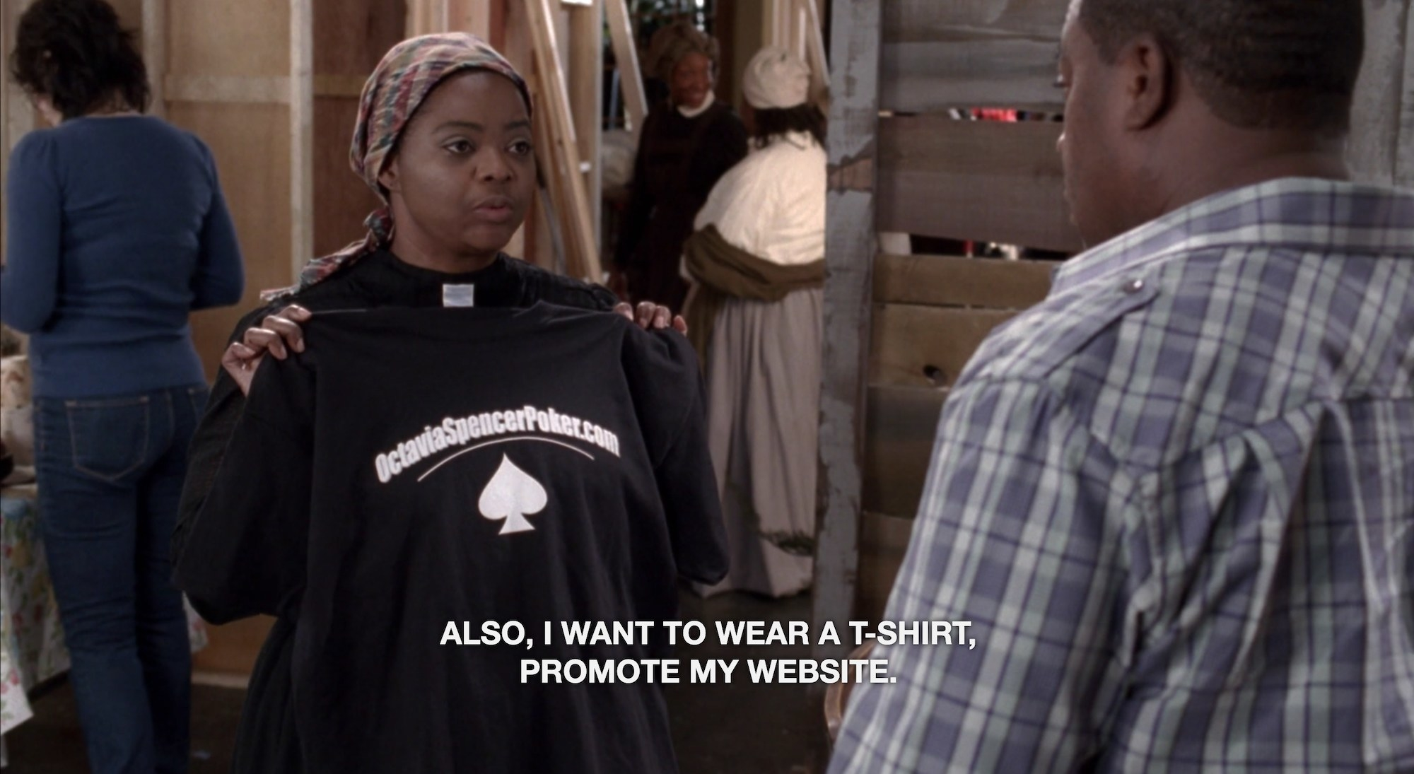 """A woman in old timey clothes holding up a T-shirt, with the caption text """"Also, I want to wear a t-shirt, promote my website"""""""