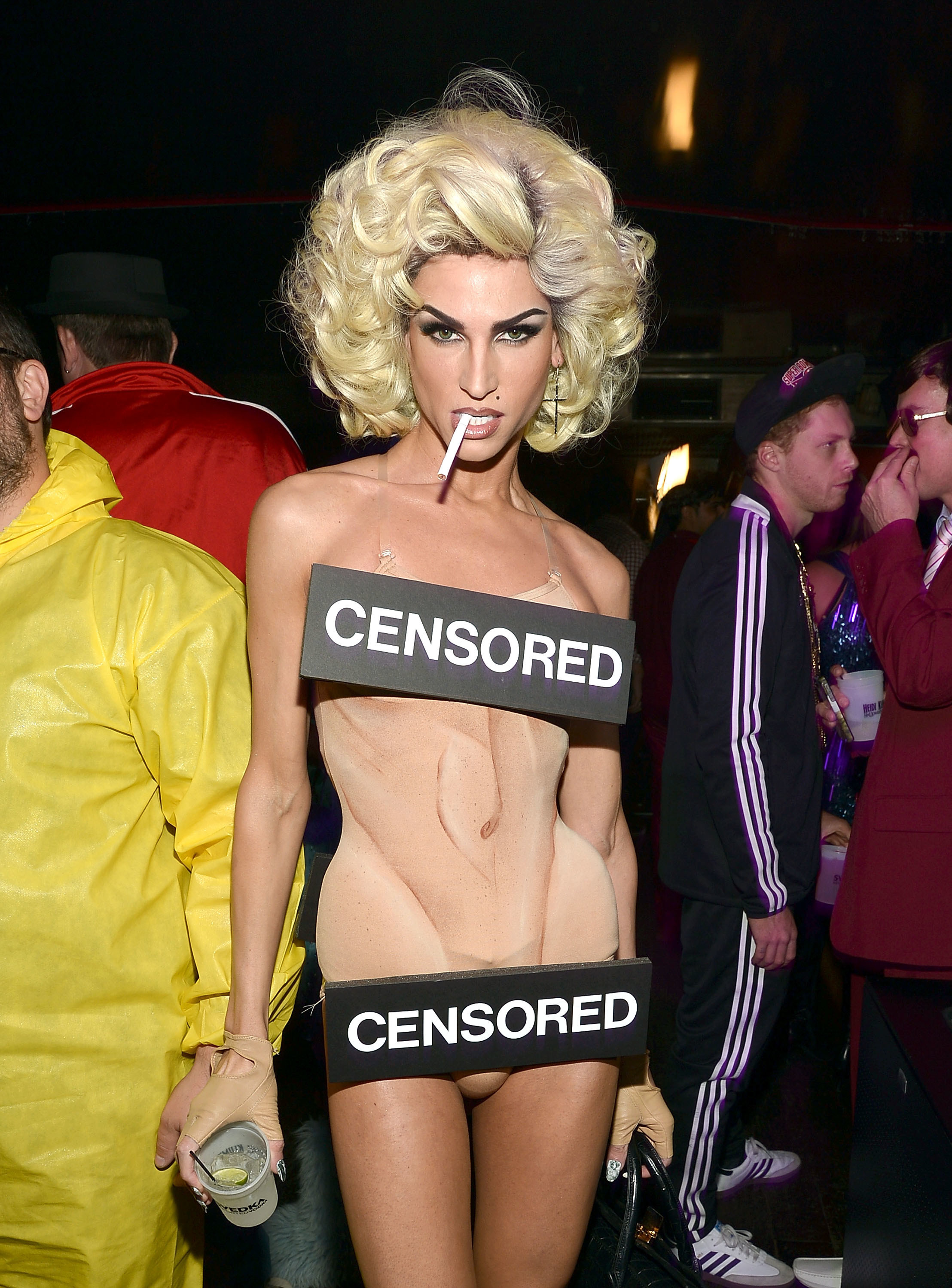 Man who appears naked with make-up and censored bars at a Halloween party.