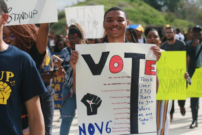 """Students hold signs in a protest that say """"Vote"""""""