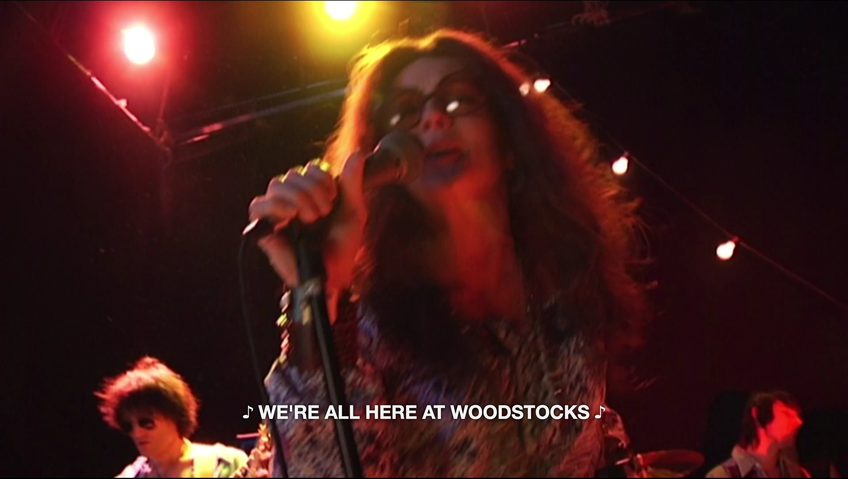 """A woman singing into a microphone with the caption text """"We're all here at Woodstocks"""""""
