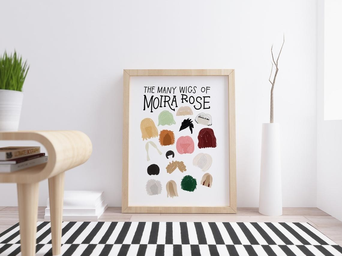 The print of Moira's wigs in a living room next to a vase