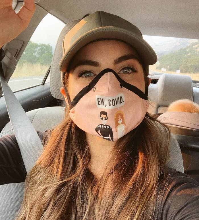 """A person wearing the """"Ew, Covid."""" face mask in their car"""