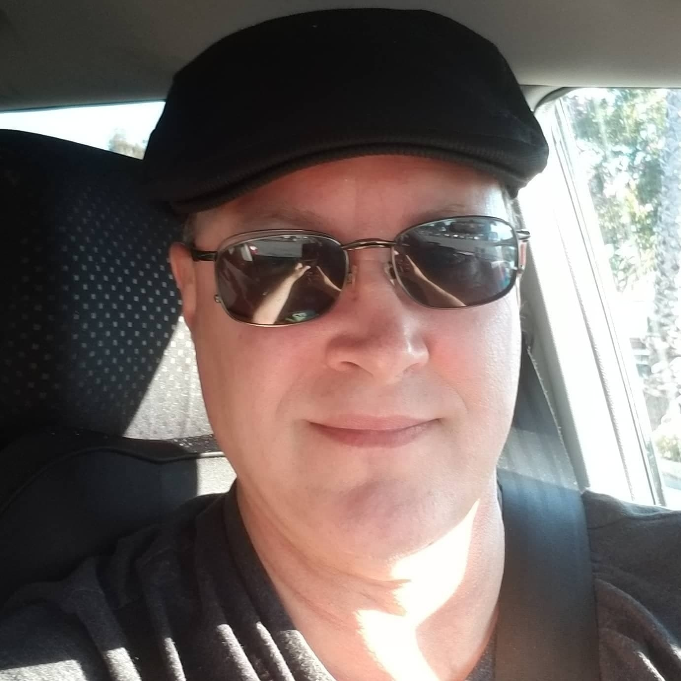 An Uber driver named Jeffrey Grant wears a black cap and sunglasses inside his car