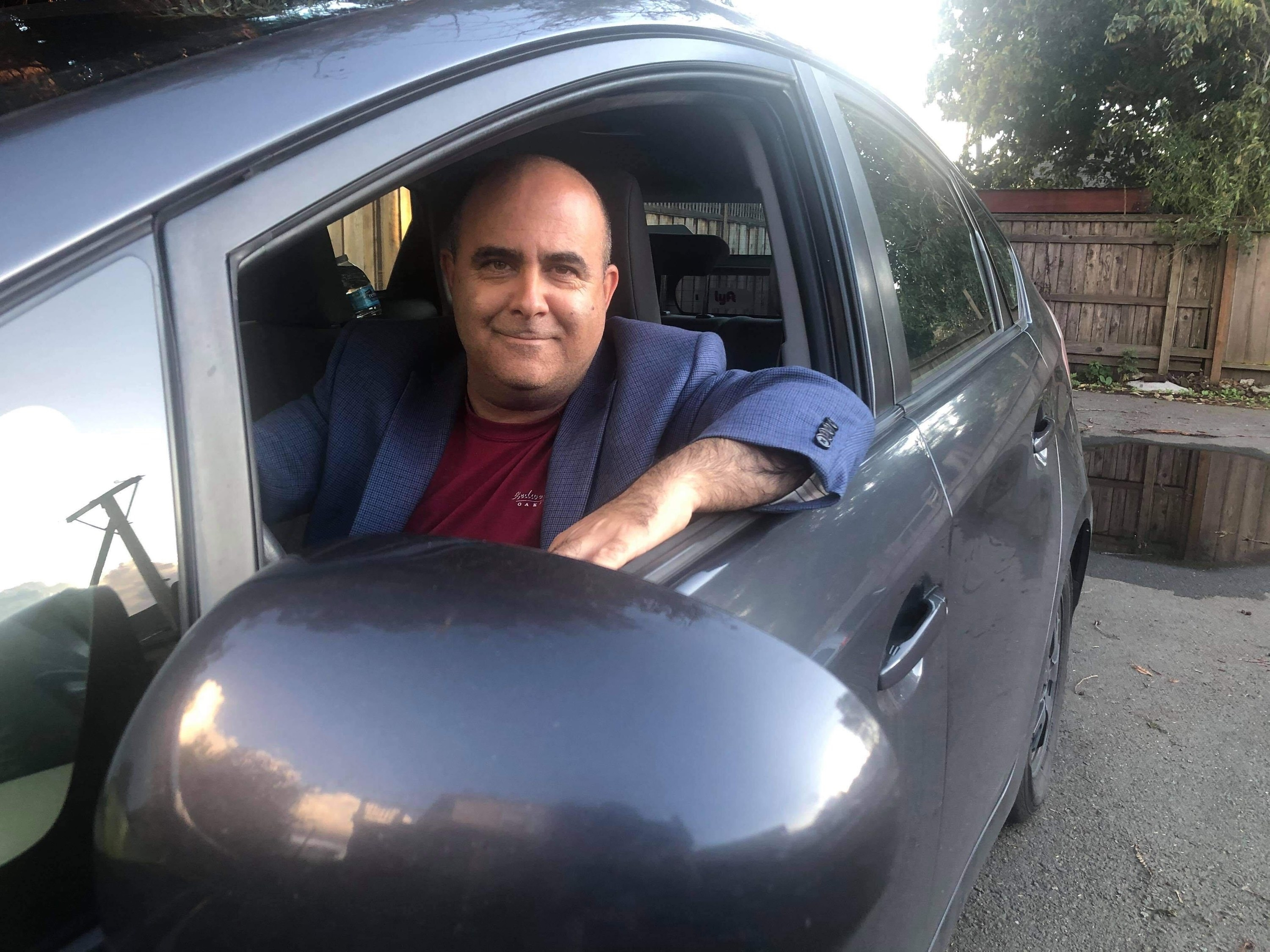 An Uber driver named Edan Alva sits in his car and smiles at the camera