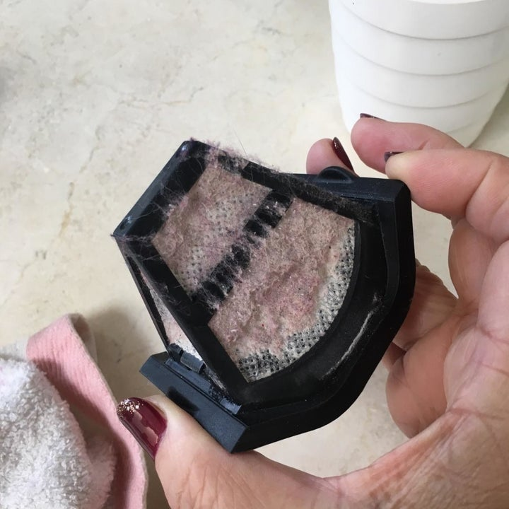 Reviewer holding the filter, which is covered in dust